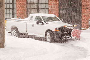 Truck with a Snowplow Clearing a Road During a Blizzard